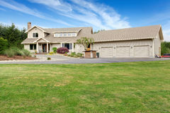 Large beige house with white trim, and well kept lawn Stock Photography