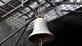 Bell on chains. A large bell hangs on chains; it is surrounded by a steel grid