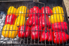 A large bell pepper in a lattice grill. Vegetables barbecue. Red and yellow peppers on grill stock photography