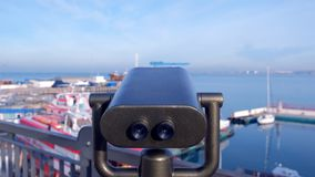 Large binoculars on the observation deck against the sea port. stock video