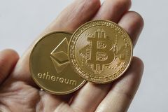 A Large Bitcoin and Etherium Token in hand. A gold Bitcoin and Etherium token in hand stock photo
