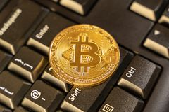 Large bitcoin on top of computer keyboard at background, cryptocurrency accepting for payment and finance concept.  royalty free stock image