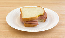 Large bitten bologna sandwich on paper plate Royalty Free Stock Images