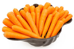 Large black bowl full of ripe and fresh carrots. On white background Royalty Free Stock Photo