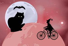 Large black cat sitting on the globe and the witch rides around the globe on a bicycle on a moonlit night in Halloween celebration Stock Photos