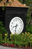 Large black clock at the entrance of the Magnolia Plantation and Gardens Charleston, South Carolina. A large black clock surrounded by flowers which can be Royalty Free Stock Photo
