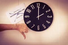 Big black clock on white wall. Time change. DST. Survey of the European Union on time change. Gesture of disagreement . Thumb down stock photography