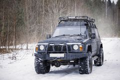 A large black expeditionary SUV. On a winter snowy road Stock Image