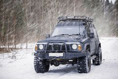 A large black expeditionary SUV. On a winter snowy road Stock Photo