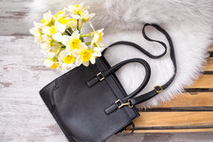 Large black female bag on white fur, daffodils. Fashionable concept, top view Stock Photos