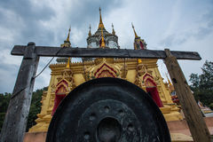 Large black gong in front of gold temple Stock Photo