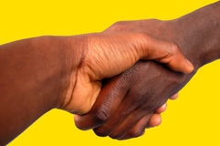 Large Black Handshake (Gold Background). This is an image of two people handshaking diagonally. (Large stock photography