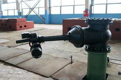 A large black metal iron gate valve with an electric drive at an industrial plant stock photography