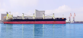 Large black red cargo ship on the water . Factory building . Sunny day. Stock Photo