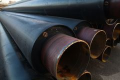 Large black steel pipe with heat insulation on the construction site close up in a plastic tube wrapper Royalty Free Stock Images