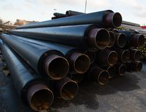 Large black steel pipe with heat insulation on the construction site in a plastic tube wrapper lying Stock Photography