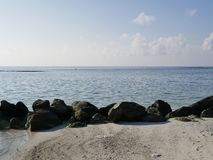 large black stones on the ocean shore of the Maldives. stock images