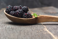 Large blackberries in an old wooden spoon. Stock Photos
