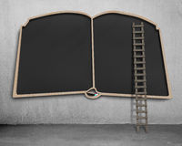Large blackboard in book shape with wooden ladder Stock Photo