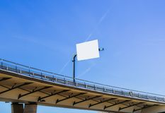 Large blank billboard at highway overpass with blue sky. Insert message accordingly stock images