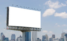 Large blank billboard on road with city view background Royalty Free Stock Photos