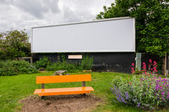 A large blank empty billboard on side of the road with bench in. A large empty advertising billboard is blank and empty read to have new adverts put up. Benches royalty free stock photography