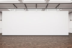 Large blank wall in an art gallery with dark wood floor Royalty Free Stock Image