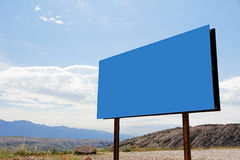 Large, blue, empty advertising sign in the mountains Stock Images