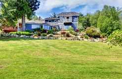 Large blue house with green hill and stone walls. Royalty Free Stock Image