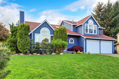 Large blue house with white trim and a nice lawn. Stock Photo