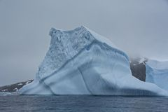 Large Blue Iceberg on a Gloomy Day in Antarctica. Large blue iceberg in Antarctic sea shows details and textures on the surface stock photography