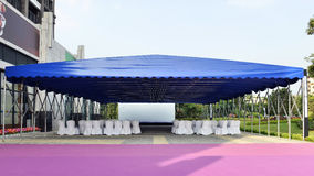 Large blue party tent. Filled with empty white chairs,wedding celebration banquet tent Stock Photo