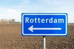Large blue sign with a white arrow in the direction of Rotterdam. Large reflective blue sign with a white arrow in the direction of Rotterdam. The traffic sign Royalty Free Stock Photography