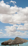 Large blue sky with clouds.Straw umbrellas Stock Photo