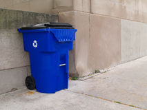 Large Blue Trash Can on a City Sidewalk. Large blue trash can with lid and wheels on an outdoor sidewalk in a city park Stock Photo