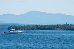 Large boat crusing on Lake Champlain. With the Green Mountains of Vermont in the background Stock Photos
