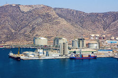 Large boat load next to a refinery stock photography