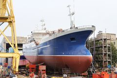 Ship is being built at the shipyard. A large boat in shore scaffolding is being built at the shipyard stock images