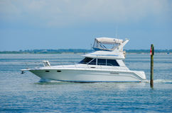 Large boat yacht cruising by channel marker Stock Photos