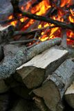Bonfire at Dusk. Large bonfire at Dusk with firewood in foreground stock photography