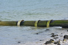 Large bore metal pipe entering sea. At low angle on sandy shore with some rocks Royalty Free Stock Photos