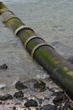 Large bore metal pipe entering sea. At low angle on sandy shore with some rocks Stock Photo