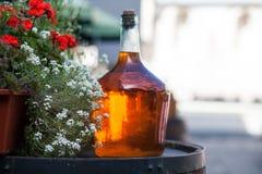 Large bottle of homemade wine are on the barrel. Vintage large wine bottle stock images