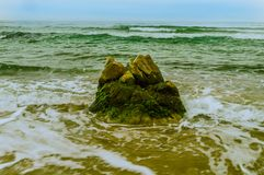 Large boulder at water edge. Large boulder at edge water in bluish green ocean under hazy blue sky Royalty Free Stock Photos