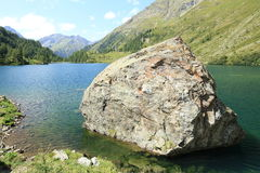 Large boulder in mountain lake. Large boulder that has rolled away from a slope above into a lake, located high in the mountains Stock Image