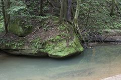 Large boulder next to stream. A large moss covered boulders next to a slow moving creek in Hocking Hills State Forest at the Old Man`s Cave area near Logan, Ohio royalty free stock photography