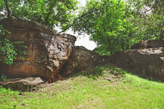 Large boulder in shade of trees Stock Photos
