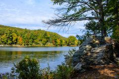 Large boulder on the shore of Breakneck Pond. Landscape featuring a boulder on the edge of Breakneck Pond in early autumn Stock Photos