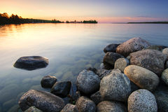 Large boulders on lake shore at sunset. Minnesota, USA Royalty Free Stock Photo