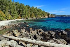 Beach at Aylard Farm in East Sooke Regional Park, Vancouver Island. Large boulders rim the fine sandy beach and the clear waters at Becher Bay in East Sooke Park Royalty Free Stock Photos
